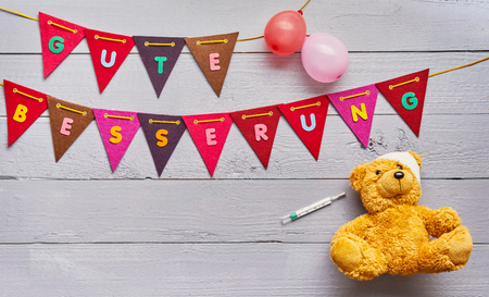Gute Besserung - Get Well - concept for kids with colorful bunting with text above a cute little teddy bear with bandage and thermometer in a paediatrics theme
