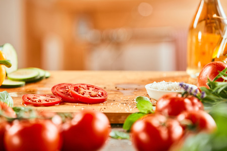 Sliced tomatoes on a wooden board with copy space above and fresh vegetables in the foreground 版權商用圖片 - 115257900