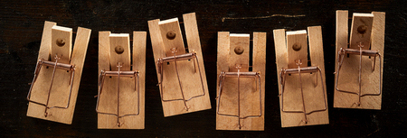 Row of spring-loaded wooden mousetraps without a bait, viewed from above on black background. Banner concept