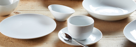 White cup on saucer and ceramic bowls on wooden table in close-up banner concept