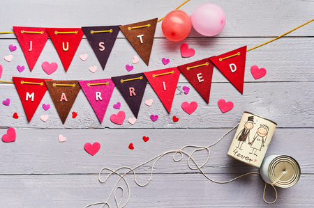 Just Married celebratory bunting with scattered hearts and decorated tin cans of the happy bridal couple over a grey wood background with copy space Imagens