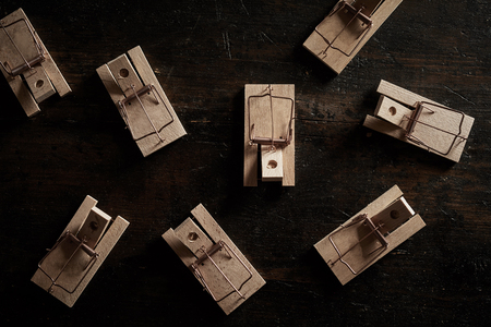 Many cocked empty wooden mousetraps sitting on dark floor and viewed from above in full frame concept