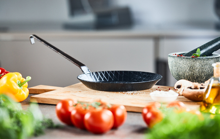 Clean empty old black skillet or pan standing on a wooden board in a kitchen with fresh vegetable ingredients Stock Photo