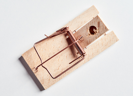 Cocked wooden mousetrap without a bait, viewed in close-up from above on white surface background