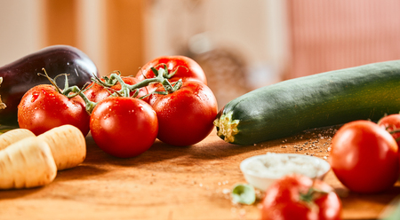 Assorted fresh vegetables on a wooden counter with zucchini, tomatoes, turnips, and brinjal or egg plant in banner format