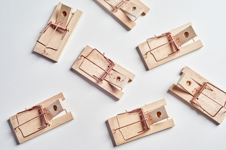 Many cocked empty mousetraps viewed from above, sitting on white surface