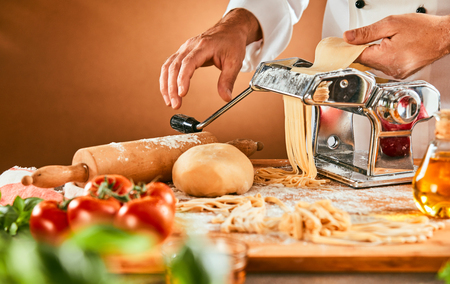 Chef preparing speciality homemade pasta noodles passing the dough through the cutter in a close up on the machine Archivio Fotografico - 115257924