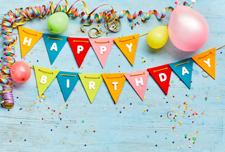 Happy Birthday bunting background with colorful triangular flags, party balloons, streamers and confetti on a blue wood background with copy space