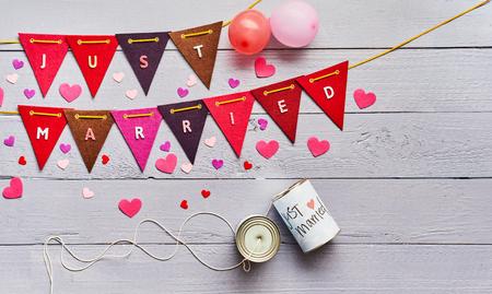 Just Married romantisches Konzept mit leuchtend rotem Ammer mit Text und verstreuten Herzen auf blauem Holzhintergrund mit Blechdosen, die für den Beginn der Flitterwochen dekoriert sind Standard-Bild