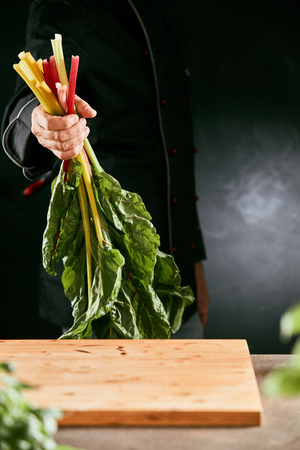 Chef holding a handful of fresh rhubarb over a wooden cutting board in a kitchen in a close up view on his hands