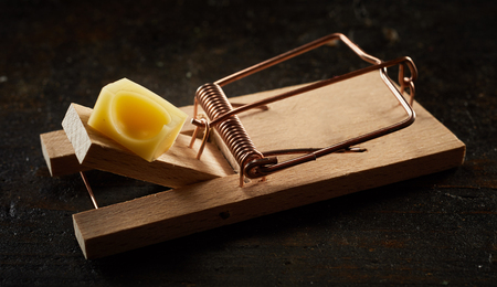 Cocked wooden spring mousetrap loaded with piece of cheese in close-up on dark background