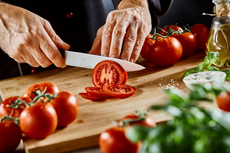 Hands of a male chef slicing a ripe tomato with a sharp kitchen knife as he prepares Italian cuisine