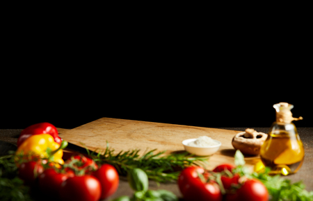 Fresh cooking ingredients around a wooden board with vegetables, herbs condiments and olive oil against a black background with copy space