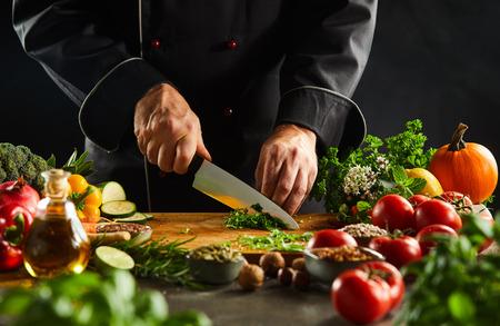 Lo chef taglia a cubetti erbe fresche su un tagliere di legno con un coltello da cucina mentre prepara l'insalata in primo piano sulle mani
