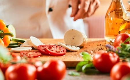 Lo chef prepara un'insalata caprese cospargendo il pomodoro a fette e la mozzarella con sale e spezie su una tavola di legno