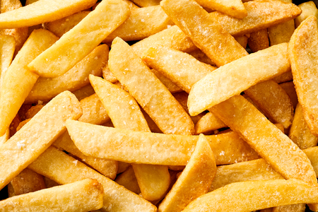 Salted homemade fried potato chips, French Fries or Pommes Frites in a close up full frame background view
