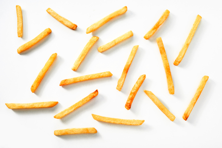 Scattered thin straight fried potato chips on a white background viewed from above Imagens