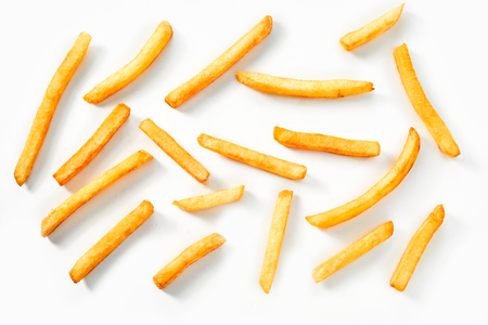 Flat lay view of deep fried crispy thin straight potato chips, French Fries or Pommes Frites on a white background