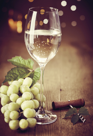 Elegant wineglass of white wine with bunch of fresh green grapes and bottle opener on a wooden table with a bokeh of sparkling party lights