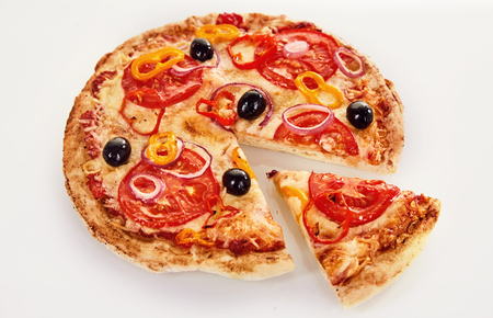 Margherita pizza topped with black olives and sliced to remove one wedge over a white background viewed high angle Banque d'images
