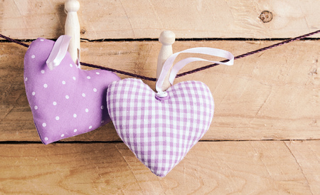 Two romantic purple hearts pegged on a line, one polka dot and one checked, tied with wooden pegs over a rustic wood background with copy space
