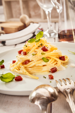 Food styling concept with Italian spaghetti with diced grilled ham or bacon and Parmesan cheese formed into a triangular tower and served at a formal table