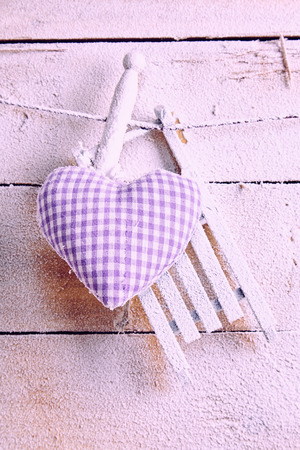 Checkered purple textile heart hanging on a line by a wooden clothe peg over textured pink wood in a love and romance concept