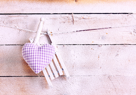 Handcrafted purple fabric heart hanging on a line with wooden pegs over a textured pink wood background with copy space and winter snow in an apres ski concept