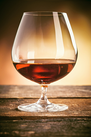 Elegant snifter with glowing French cognac served on an old rustic wood table or counter in a close up side view