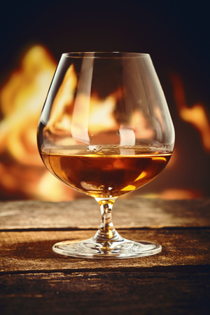 Brandy snifter with French cognac on an old rustic bar counter in front of a burning fire