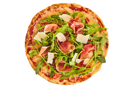 Whole oven baked Italian prosciutto and rocket pizza with a garnish of Parmesan cheese flakes viewed from above isolated on white