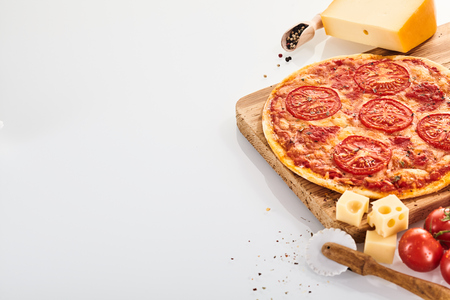 Oven-fired Italian Margherita pizza served whole on a wooden board with tomatoes, cheese and a pastry wheel cutter on white with copy space Banco de Imagens