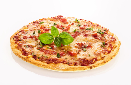 Freshly baked Italian Margherita pizza decorated with green leaf of basil. Viewed in close-up and isolated on white background 스톡 콘텐츠