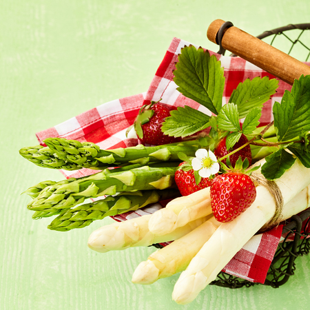 Basket with fresh green and white asparagus bunches decorated with ripe strawberry. Viewed from above in close-up