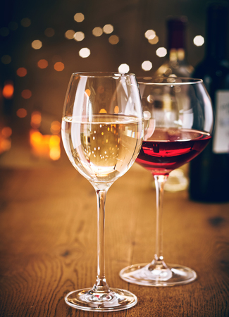 Glasses of red and white wine on a wooden table with sparkling party lights bokeh background