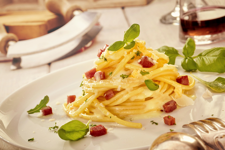 Italian spaghetti gourmet presentation in a triangular tower garnished with fresh basil and diced grilled ham or bacon in a tilted close up view