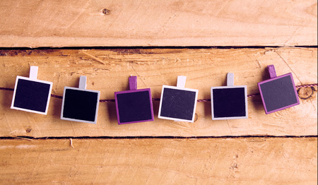 Row of blank instant photo frames hanging from pegs on a string graduating from white to purple on a rustic wood background