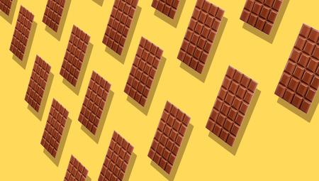 Milk chocolate tablets duplicating on yellow background with shadows viewed in perspective, and full frame.
