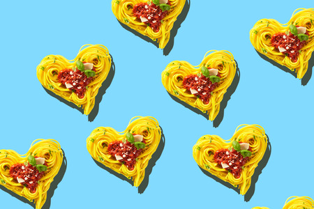 Decorative hearts of pasta of cooked yellow spaghetti with tomatoes, basil and parmesan cheese toping, viewed from above in full frame on light blue background