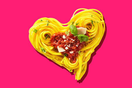 Decorative heart-shaped Italian pasta portion, formed of cooked spaghetti, topped with tomatoes, basil, and parmesan cheese, viewed in close-up, from above on pink background. Love for food concept