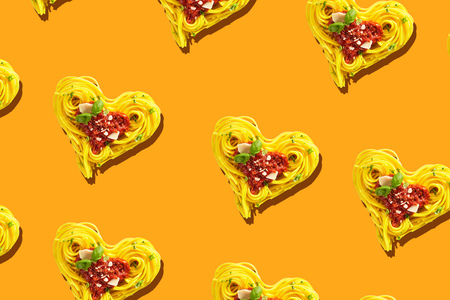 Decorative duplicating heart shapes formed of yellow spaghetti with tomatoes and parmesan cheese topping, viewed in full frame from above