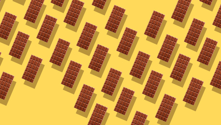 Pattern of small duplicating milk chocolate tablets on yellow background with shadows, viewed from above in full frame