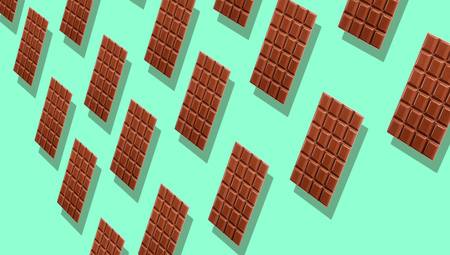 Pattern of many whole milk chocolate tablets with shadows on cyan background, viewed in perspective and full frame