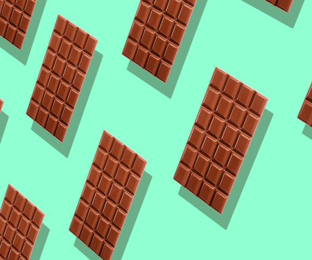 Pattern of whole delicious milk chocolate tablets hovering over green background with shadow in full frame