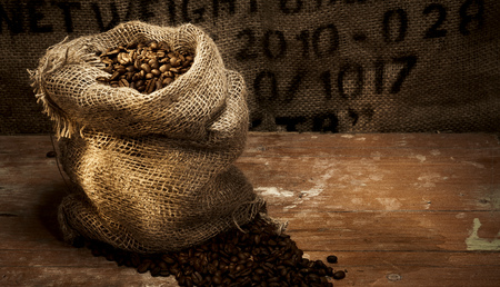 Fresh roasted coffee beans in a hessian sack on a rustic wood floor with hessian background with stencilled text and copy space for product placement 版權商用圖片