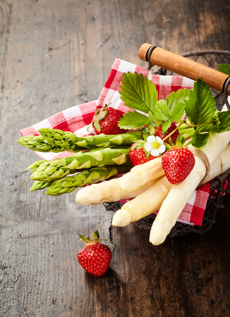 Fresh bunches of gourmet green and white asparagus tips on a checked cloth in a rustic wire basket with fresh strawberries 写真素材