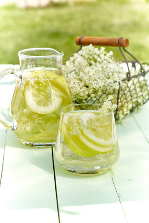 Infusion of fresh elder flowers with lemon served in a glass jug and tumbler outdoors on a green wood garden table in a concept of herbal healing, aromatherapy and alternative medicine Stock Photo