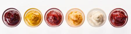 Rij van geassorteerde dips, sauzen en marinades bekeken van boven naar beneden geïsoleerd op wit in kleine glazen kommen in een panorama banner