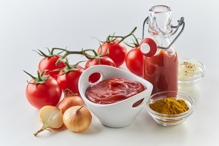 Ingredients for making tasty spicy tomato sauce with tomato puree, onion, and ground spices on a white