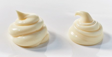 Two decorative twists of creamy mayonnaise for formal dining or presentation on white in banner format